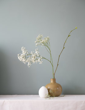A floral setting with ceramic vases filled with baby's breath and a linden branch on a white table top against a muted grey green wall.