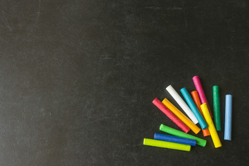 Bright pastel crayons lying on a black school board. Children's creativity. Concept-  back to school. Copy space.