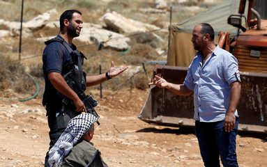 Palestinian man argues with an Israeli security guard during a protest against a new Jewish settlement outpost near Hebron in the occupied West Bank