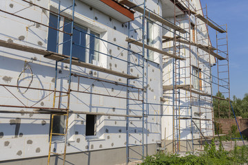 The process of building wall insulation using polystyrene in the open air. Scaffold on house,...