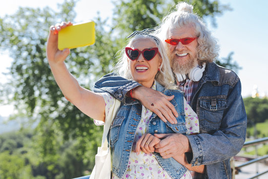 Modern device. Nice cheerful woman holding her smartphone while taking a selfie together with her husband