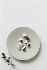 A collection of coconut bites on a neutral plate seen from above on a white surface.