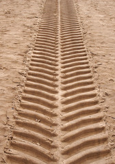 wide vertical straight single tyre print in sand running upwards with deep tread pattern