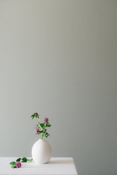 A floral setting with a ceramic vase filled with blooming clovers on a white table top against a muted grey green wall.