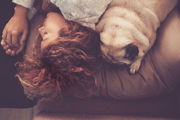 friendship and relationship concept with young beautiful woman and nice pug dog sleeping together on the bed in the morning. closer with love and sweet emotions