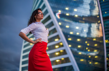 Brunette model wearing glasses, white shirt, red skirt, standing in business city