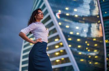 Brunette model wearing glasses, white shirt, skirt, standing in business city