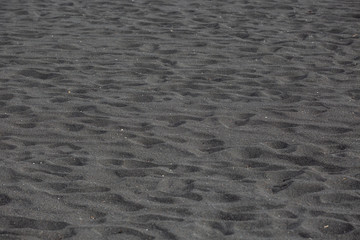 Black volcanic beach sand texture background
