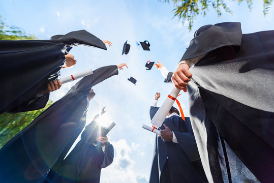 bottom view of graduated students throwing up hats in front of blue sky