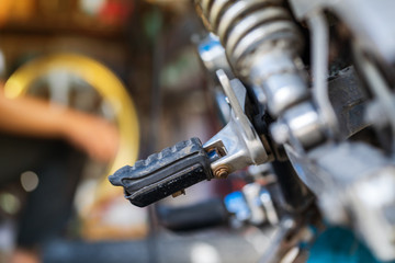Automobile mechanic repairing motorcycle in bike repair shop