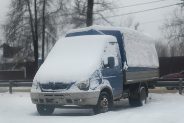 Local Winter Weather Snow Storm Covers small Delivery Truck with Snow on the parking lot.