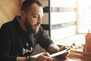 Young tattooed man holding menu, side view.