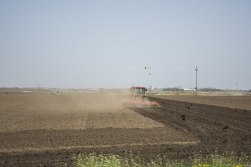 Farmer with tractor seeding - sowing crops at agricultural fields