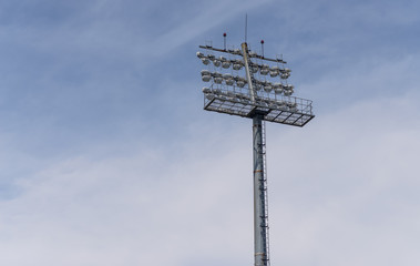 The Stadium spot-light tower over blue sky background.