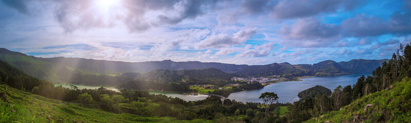 Beautiful sunset volcanic lake among mountains with green lush and trees in Ciete Cidades valley in Azores at San Miguel Island,.sunlight and clouds on the sky on background