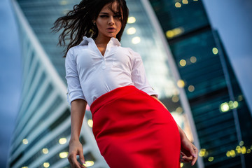 Brunette model wearing glasses, white shirt, red skirt, girl standing in business city Wall mural