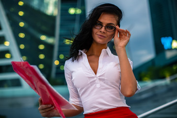 Brunette girl wearing glasses white shirt and red skirt holding folder