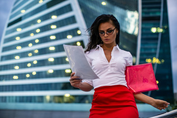 Brunette girl wearing glasses white shirt and red skirt reading documents