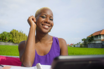 young attractive and happy successful black afro american woman working with digital tablet pad outdoors on green field cafe smiling cheerful
