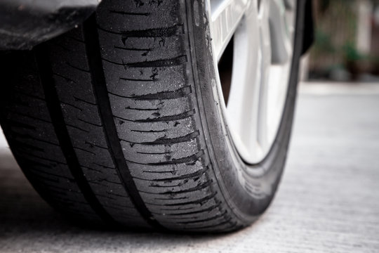 Tire wear concept. Danger of using old car bald tire with very little tread remaining.