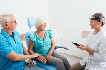 ENT Doctor talking with senior patients in doctors office