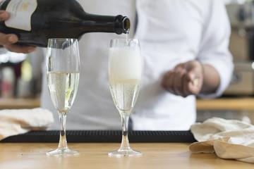 Bartender pouring champagne in flute glasses