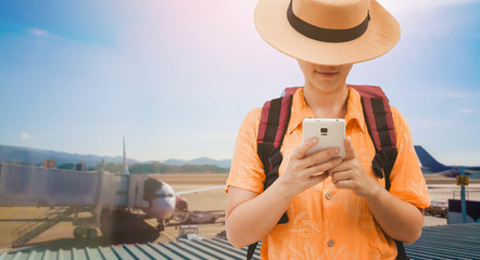 Search for apps for Book air ticket and reserve hotel concept. Asian woman traveling backpacker hiker use smart phone and touching a mobile screen on airport .
