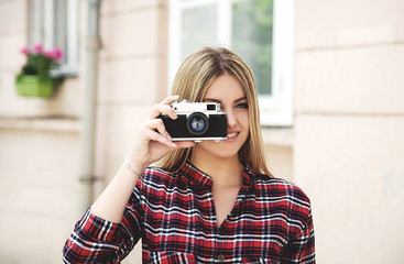 Young smiling woman with retro camera