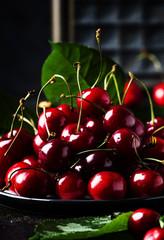 Red sweet cherries on brown table, selective focus