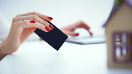 Invest in real estate concept. woman makes a payment with a credit card for the purchase of real estate on credit.