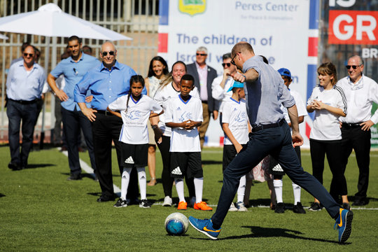 Britain's Prince William prepares to kick a ball during a soccer event with Jewish, Muslim and Christian children organized by The Equalizer and Peres Center for Peace in Jaffa, near Tel Aviv