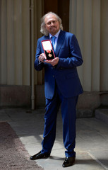 Singer and songwriter Barry Gibb, poses after being Knighted by the Britain's Prince Charles at Buckingham Palace, London