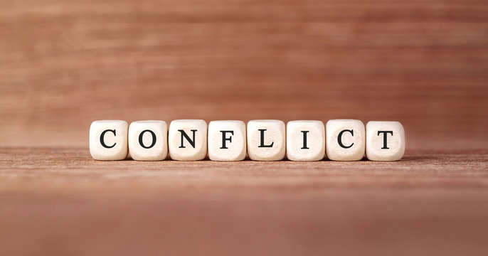 Word CONFLICT made with wood building blocks