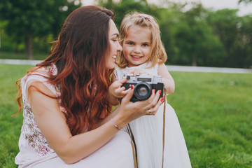 Pretty woman in light dress and little cute child baby girl take picture on retro vintage photo camera in park. Mother, little kid daughter. Mother's Day, love family, parenthood, childhood concept.