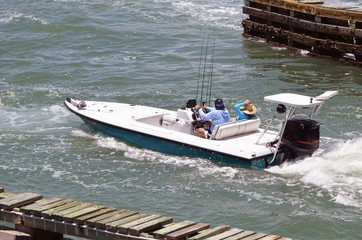 Man and a woman enjoying a week-end outing pn the Florida Intra-coastal Waterway in a sleek sport fishing boat powered by a single outboard engine.