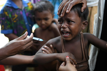 A Rohingya refugee child receives a diphtheria injection at Shamlapur refugee camp in Cox's Bazaar