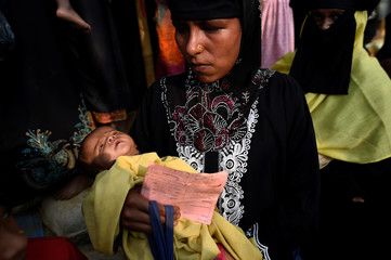A Rohingya refugee woman brings her malnourished child to the centre for malnourished children in Kutupalong refugee camp in Cox's Bazaar