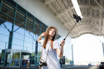 Young funny pretty traveler tourist woman with retro vintage photo camera doing selfie on mobile phone with monopod selfish stick at airport. Passenger traveling abroad on weekend. Air flight concept.