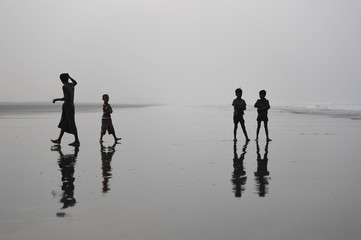 Rohingya refugee children stand on Shamlapur beach after pushing fishing boats out to sea in Cox's Bazaar
