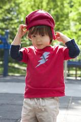 Eurasian Asian Boy Adjusting hat on playground.