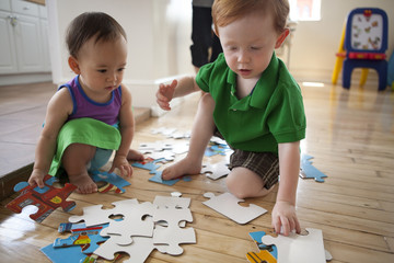 Toddlers playing with a puzzle on the floor inside