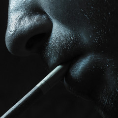 cigarette in mouth closeup on a dark background