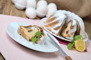 Cut of bundt cake sprinkled with sugar, lemon, melissa, milk, eggs and butter