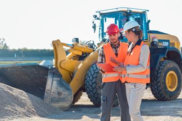 Bauarbeiter Mann und Frau auf Baustelle reden