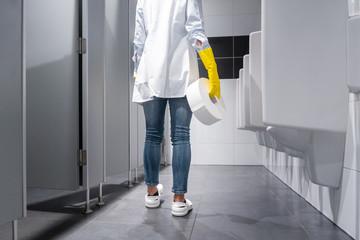 Klofrau oder Raumpflegerin wechselt Klopapier in Toilette