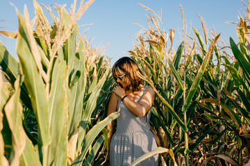 Young pretty woman standing in a green and yellow corn field. She is very happy, relaxed and carefree. Feel concept. Lifestyle.