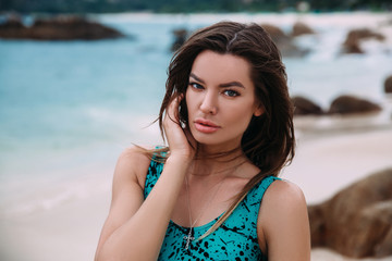 Portrait of a dark-haired beautiful woman, resting on the beach, the wind develops her long hair, the concept of rest, hotels, travel.