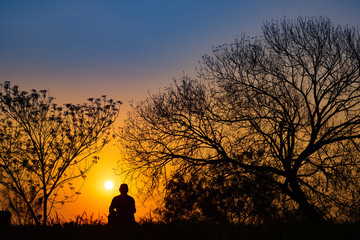 Man meditating in the field at sunrise