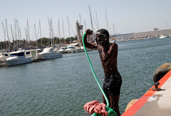 A migrant washes himself after arriving on a rescue boat at the port of Algeciras