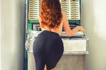 Young red hair woman in the skirt selects song on old-fashion musical jukebox. Retro style picture